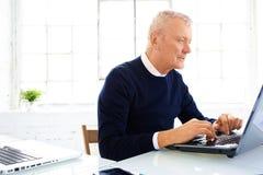 Uitvoerende bejaarde zakenman die aan laptop in het bureau werken stock foto