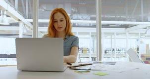 Uitvoerende gebruikende laptop in bureau 4k stock video