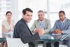 Uitvoerende gesturing duimen omhoog met recruiters tijdens baangesprek Stock Foto's