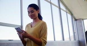 Uitvoerende macht die zich dichtbij venster bevinden en mobiele telefoon de met behulp van stock footage