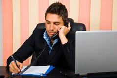Uitvoerende mens op de telefoon die nota's neemt Royalty-vrije Stock Foto's