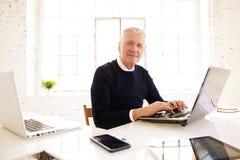 Uitvoerende professionele mensenzitting voor laptop en het werken aan nieuw bedrijfsproject stock afbeelding