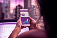 Uitvoerende vrouw op een bureau met celtelefoon in haar handen Zaken app op het scherm van smartphone Het werken bij nacht toepas stock afbeelding