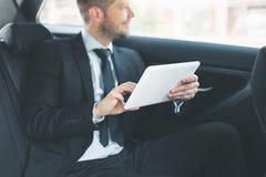 Uitvoerende zakenman bij de rug van auto die een digitale tablet gebruiken stock foto's