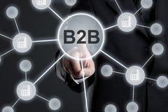 Uitvoerende zakenman in kostuum wat betreft B2B-knoop in netwerk met fabriekspictogrammen op virtueel touch screen - zaken aan za stock afbeelding