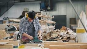 Uitzoomen van mannelijk timmermans oppoetsend hout met riemschuurmachine die in fabriek werken stock videobeelden