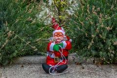 Ujmujący Święty Mikołaj obsiadanie po środku ogródu Zdjęcie Stock