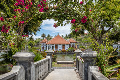 Ujung Water Palace through Bougainvillea archway, Bali Island, Indonesia. Ujung Water Palace, Karangasem, Bali Island, Indonesia Royalty Free Stock Photos