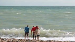 UK, Μπράιτον Το νέοι ζεύγος και ο φίλος είναι στην ακτή του Ατλαντικού Ωκεανού Ένα ζεύγος αγκαλιάζει, ένα κορίτσι στέκεται την πλ φιλμ μικρού μήκους