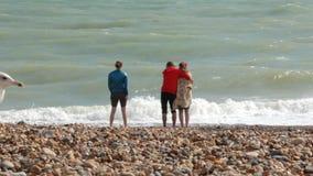 UK, Μπράιτον Το νέο ζεύγος και ένα κορίτσι είναι στην ακτή του Ατλαντικού Ωκεανού Ένα ζεύγος αγκαλιάζει, ένα κορίτσι στέκεται την απόθεμα βίντεο