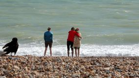 UK, Μπράιτον Το νέο ζεύγος και μια νέα γυναίκα είναι στην ακτή του Ατλαντικού Ωκεανού Ένα ζεύγος αγκαλιάζει, ένα κορίτσι στέκεται απόθεμα βίντεο