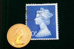 UK blue stamp with portrait of Elizabeth II and 1980 Australian Gold sovereign on  black background Royalty Free Stock Photography
