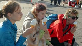 UK, Brighton. Two girls and a guy on summer vacation enjoying ice cream in cones at the oceanfront. Teenage hipster. Friends have a rest. Sunny day stock video footage
