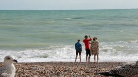 UK, Brighton. Two girls and a guy on summer vacation standing on the beach near the water of Atlantic ocean. The guy stock video footage