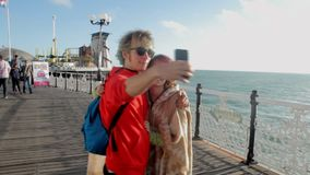 UK, Brighton. Young couple taking selfie photo. Happy lovers traveling on vacation on ocean enjoying romance. Young. Caucasian woman and man. Rest stock video