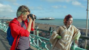 UK, Brighton. Young guy taking photo of hipster girl on the coast. Happy lovers, woman and man traveling on vacation on. Ocean. Girl leaning on railing of beach stock video footage