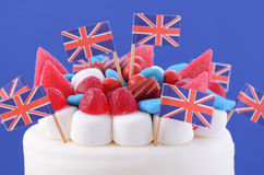 UK celebration cake. With flags, marshmallow and candy decorations on a red cake stand on a white table against a blue background Stock Image