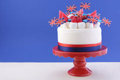 UK celebration cake. With flags, marshmallow and candy decorations on a red cake stand on a white table against a blue background Stock Images