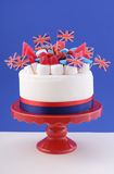 UK celebration cake. With flags, marshmallow and candy decorations on a red cake stand on a white table against a blue background Royalty Free Stock Photos
