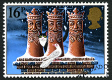UK Christmas Postage Stamp. GREAT BRITAIN - CIRCA 1983: A used postage stamp from the UK, depicting a festive illustration of a cat and dove on a rooftop with Royalty Free Stock Photography