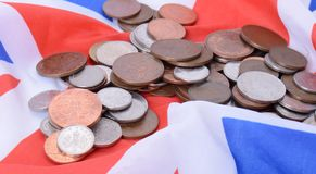 Uk coins on uk Flag. British coins on the UK flag Royalty Free Stock Photos