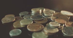 UK Currency pounds coins rotating amongst other UK currency coins in 4K. Business Background stock footage