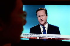 UK Election TV Debate. A viewer watches Conservative Party PM David Cameron on a live election debate streaming over the internet and broadcast on TV on April 2 Royalty Free Stock Image
