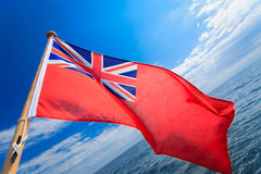 UK ensign british maritime flag of yacht sailboat blue sky sea. Sailing. UK ensign british maritime flag of yacht sailboat. blue sky and sea in background Royalty Free Stock Image