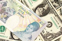 UK fem pund anmärkning på en bakgrund av en dollar räkningar arkivbild