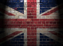 UK flag on a brick wall background. Union flag on a brick wall background with top light and dark vignette Royalty Free Stock Image