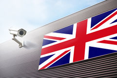 Uk flag and cctv camera. Conceptual United Kingdom flag and security camera on the new metal wall building. Conceptual political relations with neighbors Stock Image