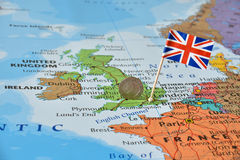 UK flag and coin on map, political or financial crisis concept. Paper flag pin of the United Kingdom and British pound sterling coin on a map, political or stock photo