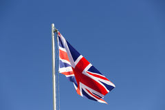 UK flag on a flagpole. In front of blue sky Royalty Free Stock Photography