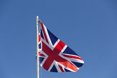 UK flag on a flagpole. In front of blue sky Stock Photos