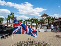 UK flag with beautiful background near a stage. UK flag near a stage in Therme Balotesti in Romania at a concert with people ,pslm trees and sky with clouds in stock images