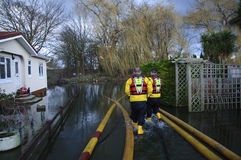 2014 UK Floods. UK Chertsey -- 20 Feb 2014 -- Fireman Steve Evans R and Darryl Gwilt from Mid & West Wales Fire & Rescue Service wade into floodwater in Chertsey Royalty Free Stock Image