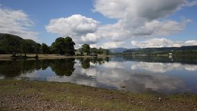 UK Lake District Ullswater Cumbria England. With mountains and blue sky on beautiful still summer day with water reflections from sunny weather stock footage