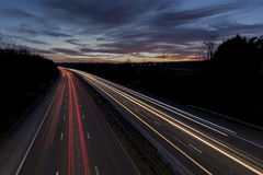 A UK motorway, at sunset, with light trails created by the traffic. On the road Royalty Free Stock Images