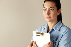 UK nurse holding clipboard. Looking past camera Stock Photo