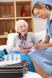 UK nurse visiting senior woman at home. UK nurse visiting senior women at home writing on her chart Stock Photo