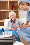 UK nurse visiting senior woman at home Stock Photo