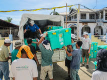 UK overseas aid workers loading ShelterBox emergency aid onto trucks after Typhoon Haiyan in the Philippines Royalty Free Stock Photography