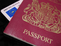 UK Passport and Drivers License. UK Passport and drivers licnense in close-up against a dark background stock photo