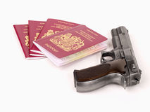 UK passport and gun. UK passports and a handgun on white background Royalty Free Stock Photos