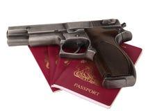 UK passport and gun. UK passports and a handgun on white background Stock Photography