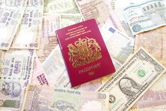 UK Passport on Various Currencies. United Kingdom passport on various international currency bills Stock Photography