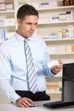 Uk-pharmacist som fungerar på datoren Fotografering för Bildbyråer