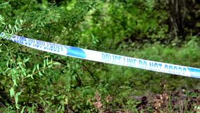 UK Police Tape In Front Of Wooded Undergrowth