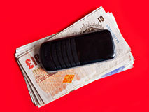 UK pounds - money and mobile phone. Hmmm....something to do with the recent spate of phone tapping allegations by any chance? UK pounds sterling, with phone Royalty Free Stock Images