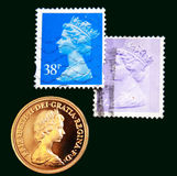 UK purple and blue stamps with portrait of Elizabeth II and 1980 Australian Gold sovereign on  black background Stock Photo